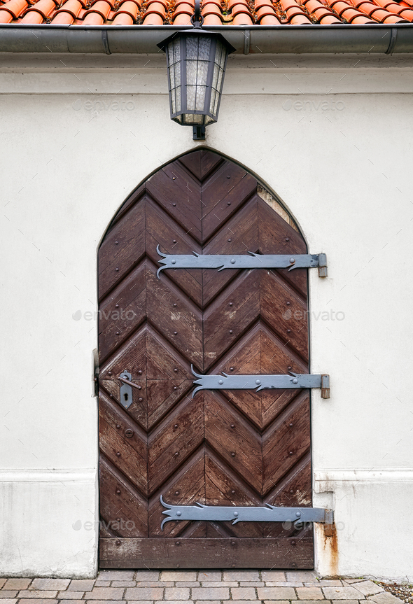 Old wooden door with a lamp above - Stock Photo - Images