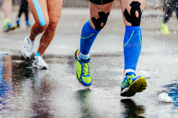 legs runner in compression socks and kinesiology tape - Stock Photo - Images