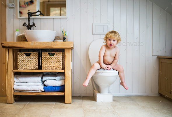 Cute toddler boy sitting on the toilet in the bathroom. - Stock Photo - Images