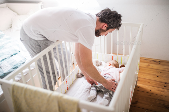 Father putting a sleeping toddler girl into cot at home. - Stock Photo - Images