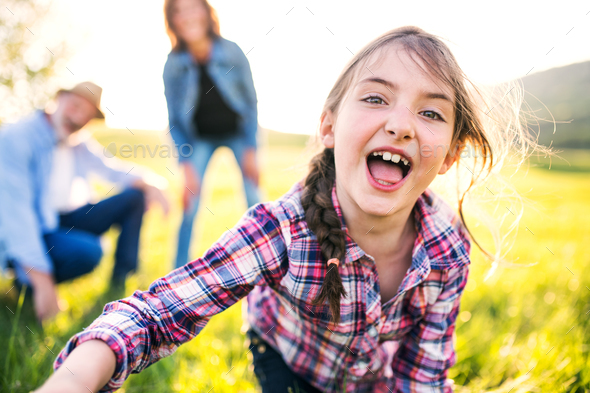 A small girl with her senior grandparents having fun outside in nature. - Stock Photo - Images