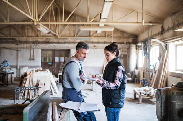 Man and woman workers working in the carpentry workshop. - Stock Photo - Images