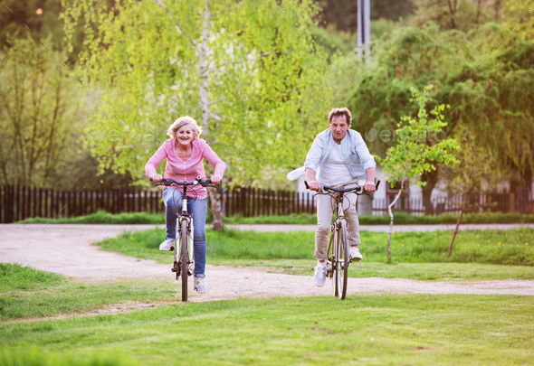 Beautiful senior couple with bicycles outside in spring nature, cycling. - Stock Photo - Images