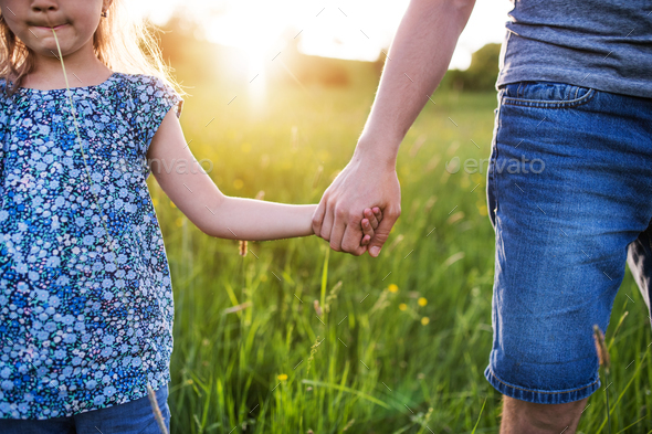 Father with a small daughter on a walk in spring nature at sunset. - Stock Photo - Images