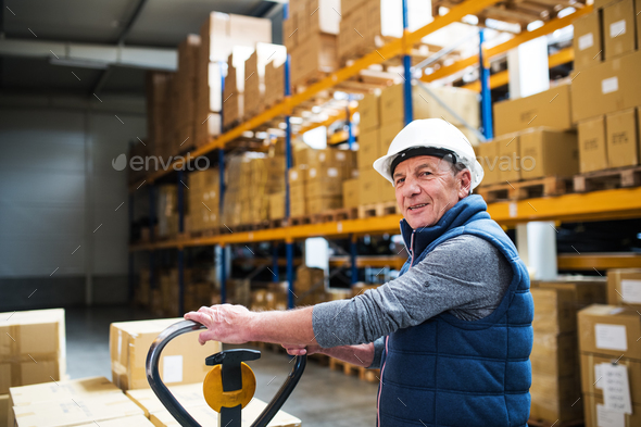 Senior male warehouse worker or a supervisor pulling a pallet truck with boxes. - Stock Photo - Images