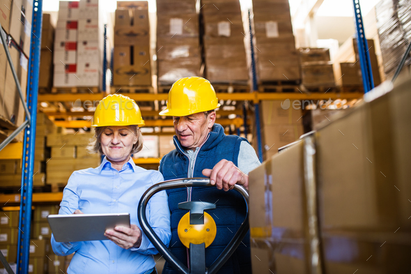 Senior woman manager and man worker with tablet working in a warehouse. - Stock Photo - Images