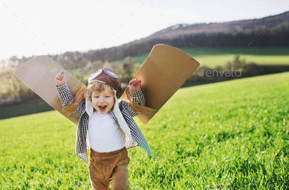 Happy toddler boy with wings playing outside in spring nature. - Stock Photo - Images