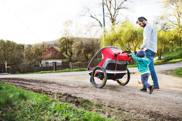 A father with toddler son pushing a jogging stroller outside in spring nature. - Stock Photo - Images