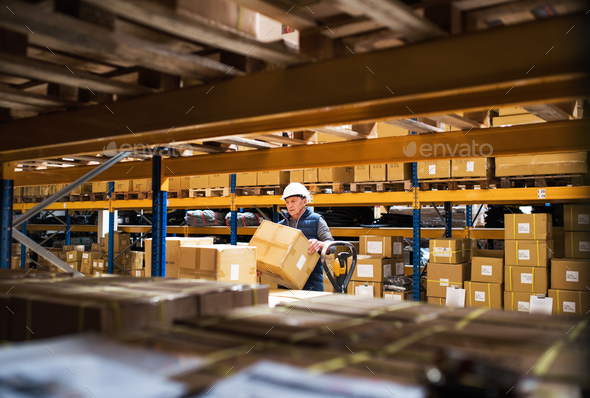 Senior male warehouse worker or a supervisor unloading a pallet truck with boxes. - Stock Photo - Images