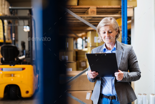 Senior woman warehouse manager or supervisor with clipboard. - Stock Photo - Images