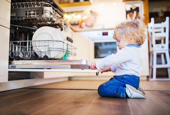 Toddler boy in dangerous situation at home. Child safety concept. - Stock Photo - Images