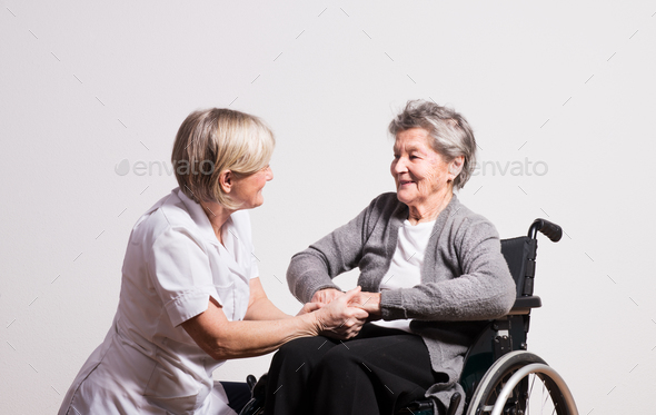 Studio portrait of a senior nurse and an elderly woman in wheelchair. - Stock Photo - Images
