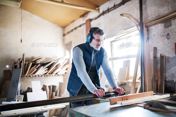 A man worker in the carpentry workshop, working with wood. - Stock Photo - Images