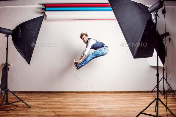 Portrait of a young hipster man in a studio, jumping. Copy space. - Stock Photo - Images