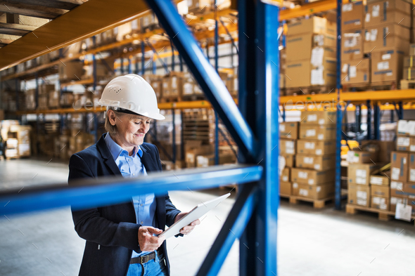 Senior woman warehouse manager or supervisor with tablet, working. - Stock Photo - Images