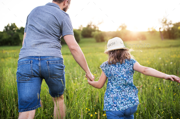 Father with a small daughter on a walk in spring nature. - Stock Photo - Images