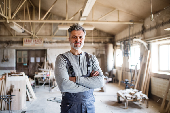 Portrait of a man worker in the carpentry workshop. - Stock Photo - Images