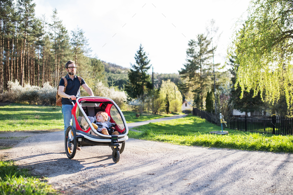 A father with two toddlers in jogging stroller on a walk outside in spring nature. - Stock Photo - Images