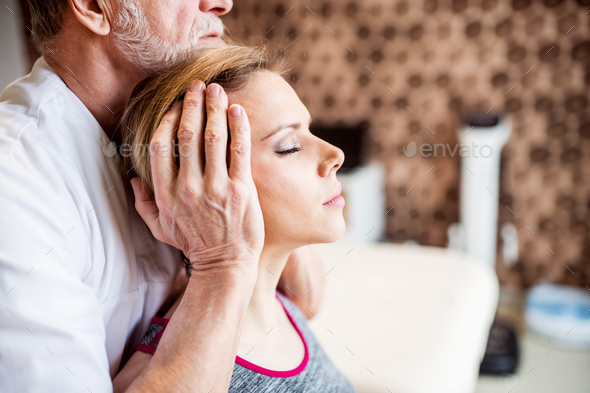 Senior male physiotherapist working with a female patient. - Stock Photo - Images