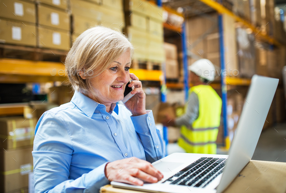 Senior woman manager with smartphone and man worker working in a warehouse. - Stock Photo - Images