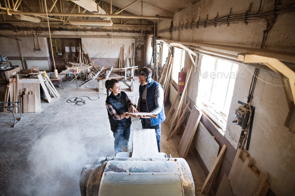 Man and woman workers in the carpentry workshop holding wood. - Stock Photo - Images