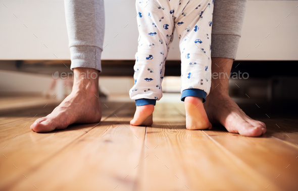Legs of father and a toddler boy standing on the floor in bedroom at home. - Stock Photo - Images