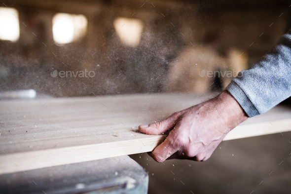 An unrecognizable man worker in the carpentry workshop, working with wood. - Stock Photo - Images