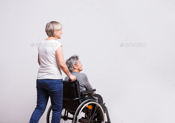 Studio portrait of a senior woman in wheelchair with a carer. - Stock Photo - Images