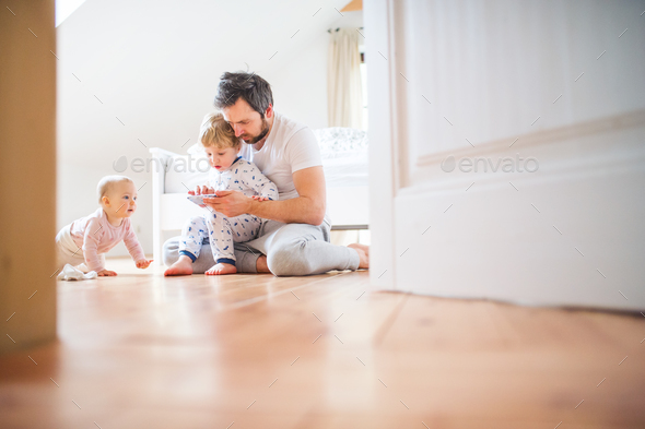 Father and toddler children with smartphone at home at bedtime. - Stock Photo - Images