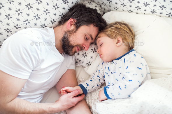 Father holding hand of a sleeping toddler boy in bed at home. - Stock Photo - Images