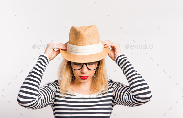 Portrait of a young beautiful woman in studio, holding a hat. - Stock Photo - Images