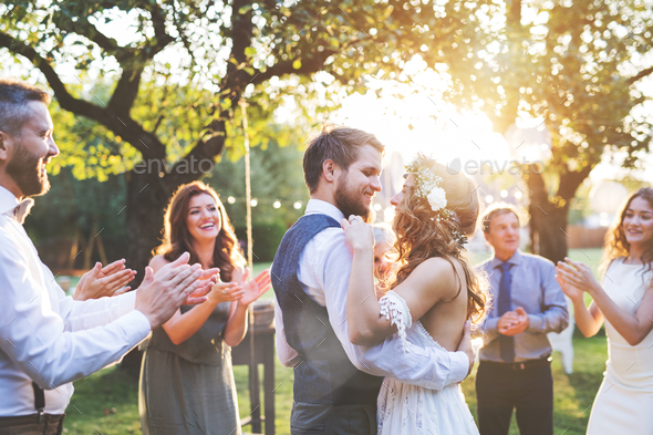 Bride and groom dancing at wedding reception outside in the backyard. - Stock Photo - Images