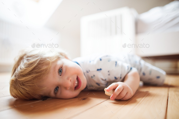 A toddler boy on the floor in the bedroom at home. - Stock Photo - Images