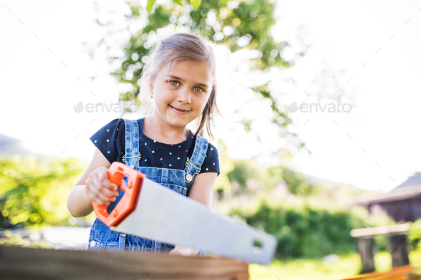 A small girl with a saw outside, making a wooden birdhouse. - Stock Photo - Images