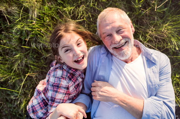 A small girl with grandfather outside in spring nature, relaxing on the grass. - Stock Photo - Images