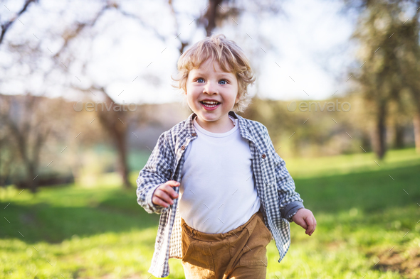 Happy toddler boy running outside in spring nature. - Stock Photo - Images