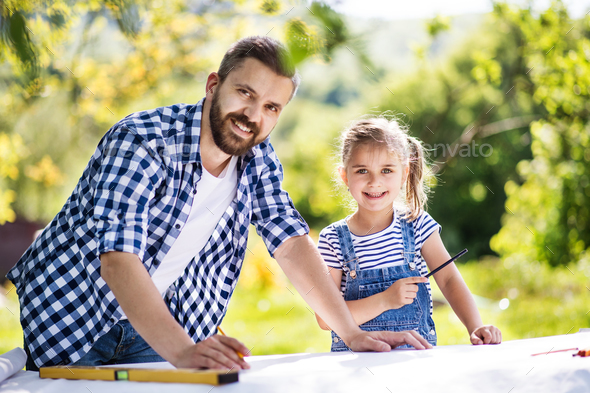 Father with a small daughter outside, planning wooden birdhouse. - Stock Photo - Images