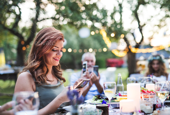 Guests with smartphones taking photo at wedding reception outside. - Stock Photo - Images