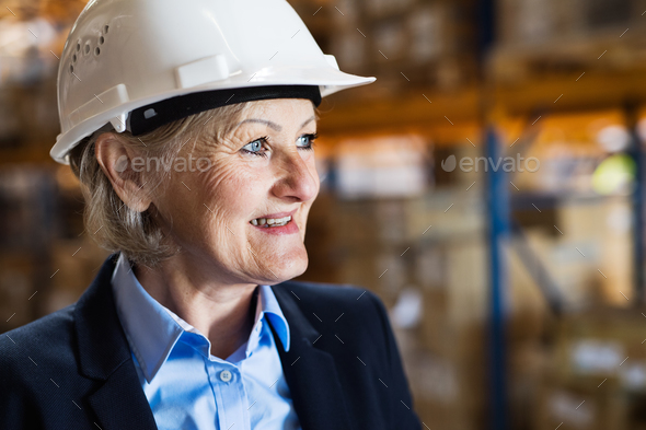 Senior woman warehouse manager or supervisor with white helmet. - Stock Photo - Images