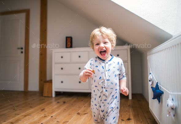 A toddler boy in the bedroom at home. - Stock Photo - Images