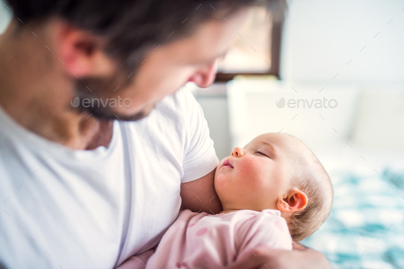 Father holding a sleeping toddler girl at home. - Stock Photo - Images
