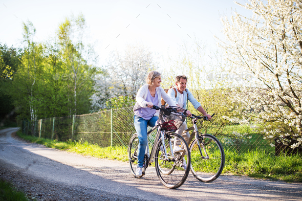 Senior couple with bicycles outside in spring nature. - Stock Photo - Images