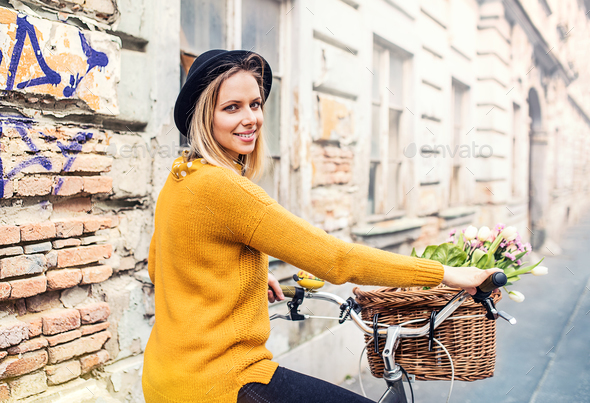 Young woman with bicycle and flowers in sunny spring town. - Stock Photo - Images