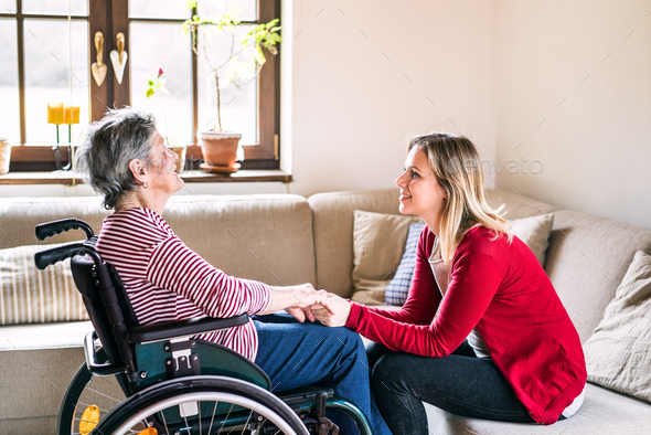An elderly grandmother in wheelchair with an adult granddaughter at home. - Stock Photo - Images