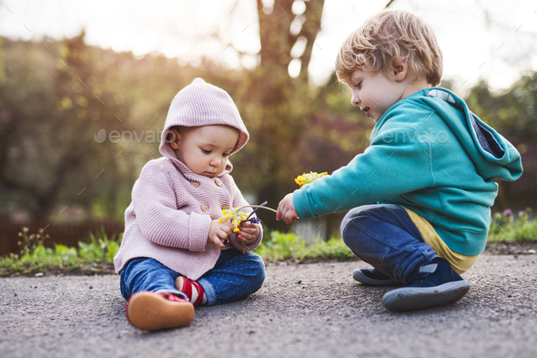 A toddler boy and girl outside on a spring walk. - Stock Photo - Images
