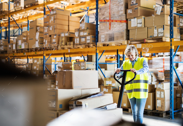 A senior woman warehouse worker pulling a pallet truck with boxes. - Stock Photo - Images
