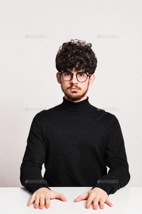 Young man in a studio, sitting at the table. - Stock Photo - Images