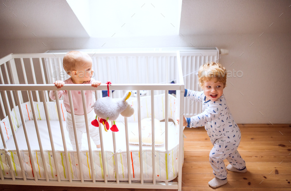 Two toddler children in bedroom at home. - Stock Photo - Images