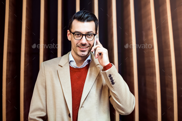 Young man with smartphone standing against wooden wall. - Stock Photo - Images