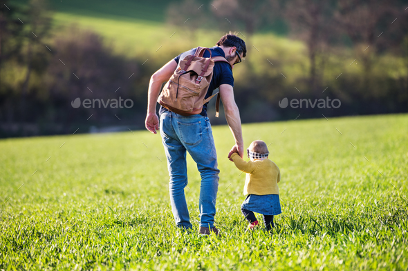 A father with his toddler daughter on a walk outside in spring nature. - Stock Photo - Images